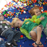 Children on floor covered in craft supplies