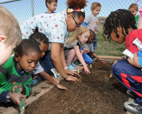 Teacher and children playing in dirt