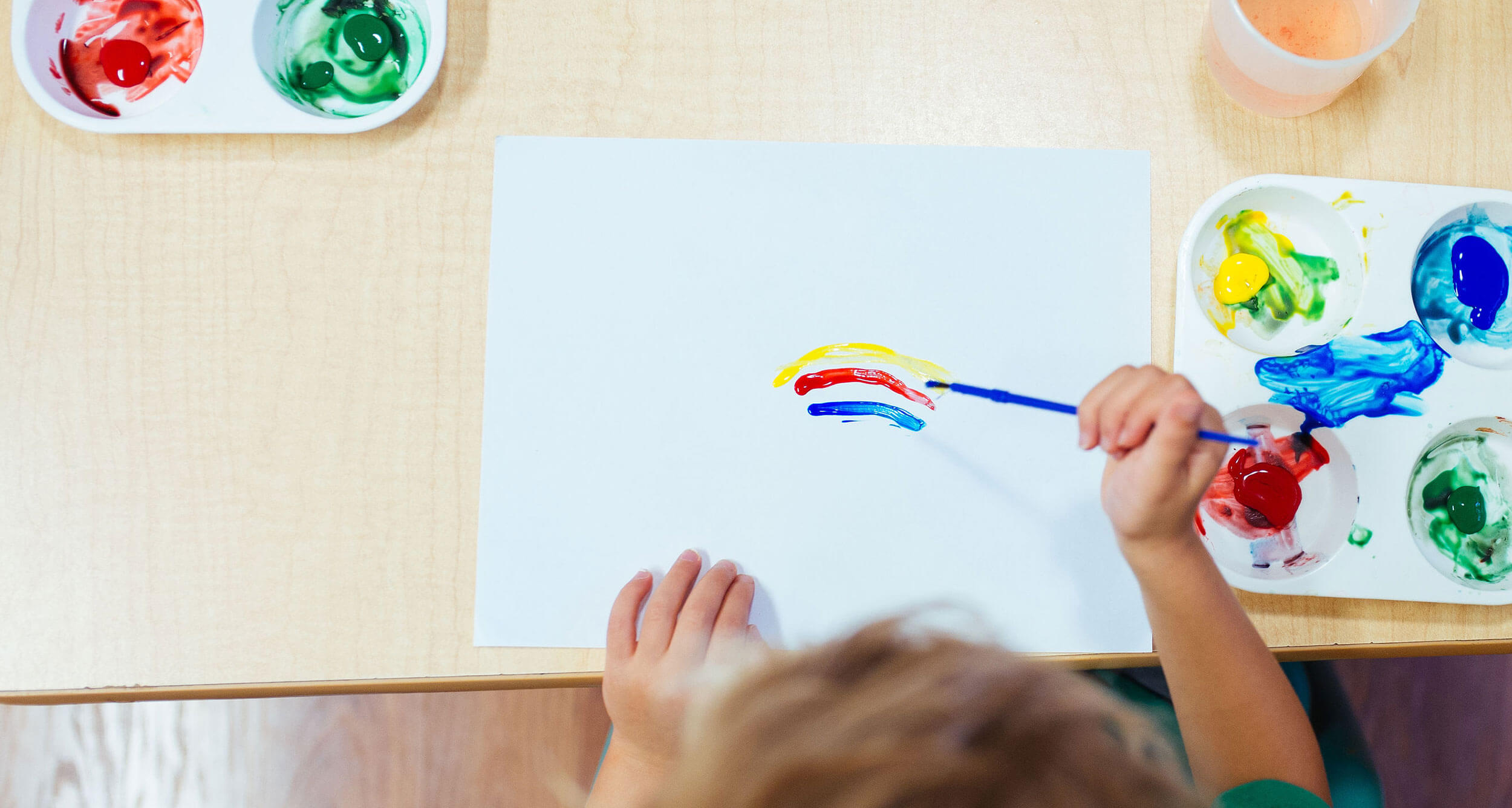 Picture of young white child painting a rainbow